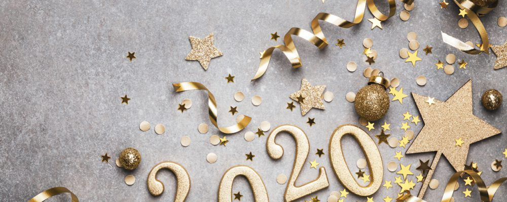 Holiday background with golden Christmas decorations and New year 2020 numbers and confetti stars top view with copy space.