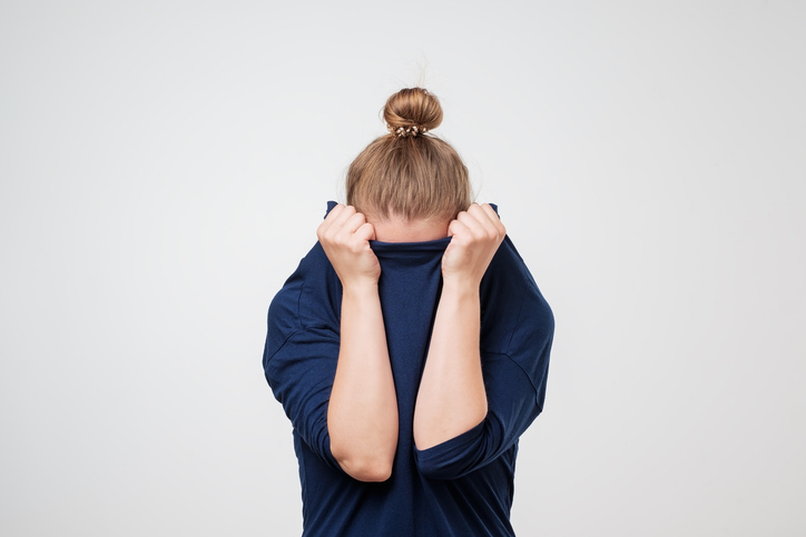 A woman with migraine who is hiding her face in her dark blue sweater.