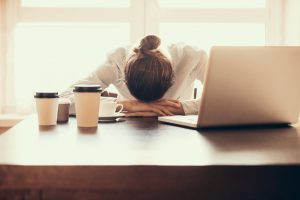 A woman sitting at an office desk with her head in her hands, having a migraine attack