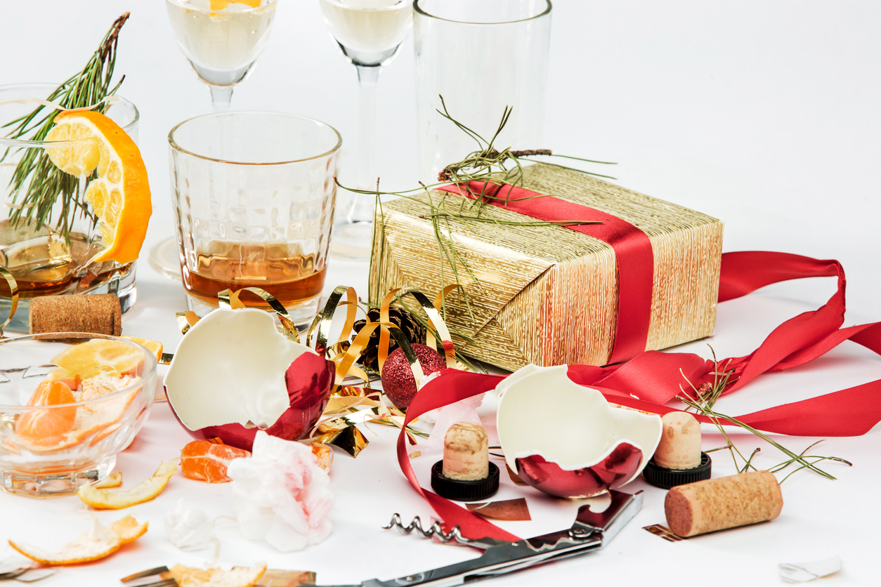 Empty or half-empty glasses with liquor, wrapped Christmas presents and broken Christmas decoration lying on a table, symbolizing different migraine triggers.