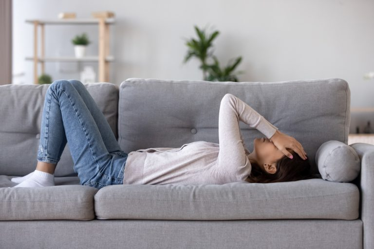 Young woman lying on a couch with a migraine.